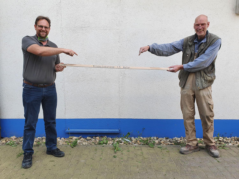 Werkstattleiter Rainer Speker (l.) und Schreinermeister Thomas Finis zeigen die Abstandshilfe der Lebenshilfe. Foto: Uwe Meyer / Lebenshilfe