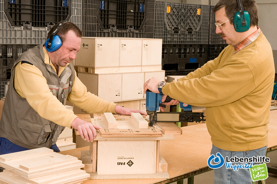 Mitarbeiter der Lebenshilfe-Schreinerei arbeiten an der Transportbox für die Firma Schaeffler.