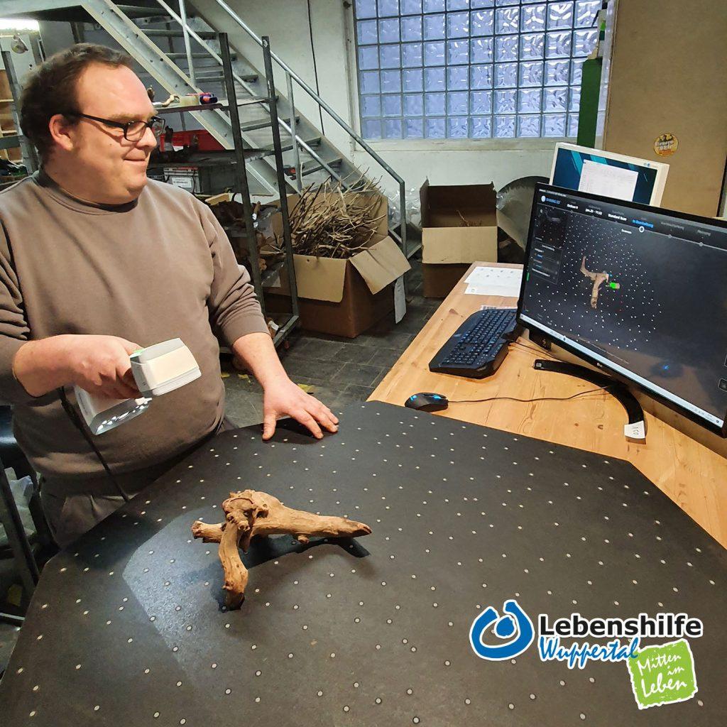 Der Lebenshilfe-Mitarbeiter scannt Aquarium-Wurzeln ein.