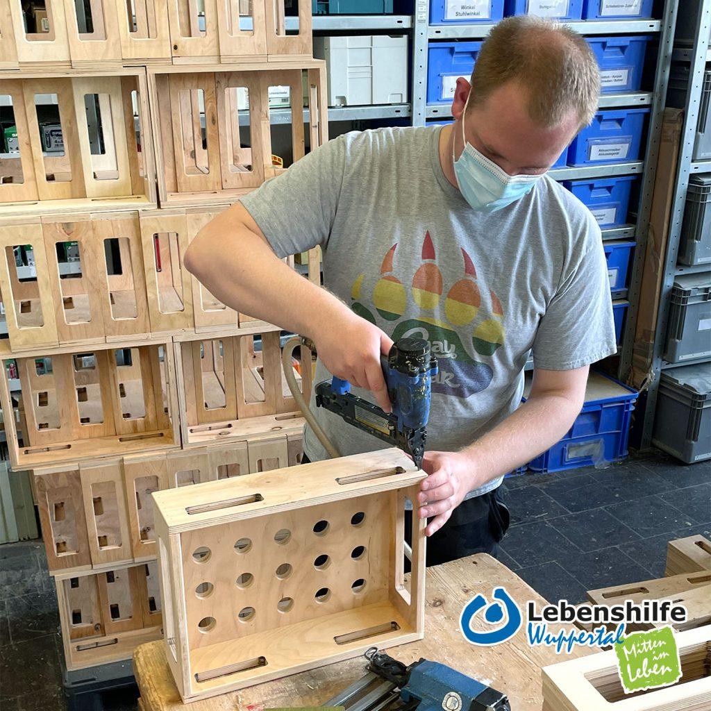 Marcel Wilms arbeitet in der Lebenshilfe-Werkstatt an einer Transportbox für die Firma WASI.